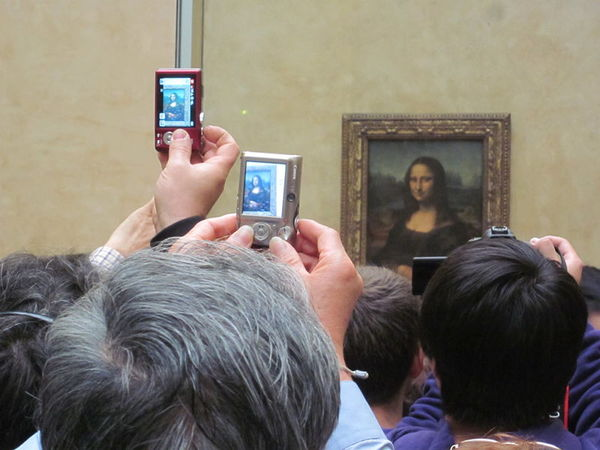 People taking pictures of the Mona Lisa in the Louvre